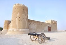 A vintage canon & Zubarah fort, Qatar. The Zubarah Fort built in 1938 follows a traditional concept with a square ground plan with towers at the corner Royalty Free Stock Images