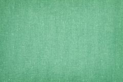 Vintage canvas background. Vintage torn canvas background with dark borders and green color textile stock photos