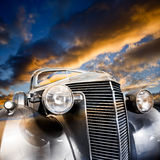 Vintage Car. Front-view of silver colored vintage car bonnet, under a colorful sky in the evening Royalty Free Stock Image