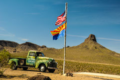 Vintage car in the arizona desert with national and state flags Royalty Free Stock Images
