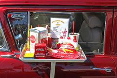 Vintage car with classic drive in food. Interior of a Classic American car parked at a car show with drive in food Royalty Free Stock Image
