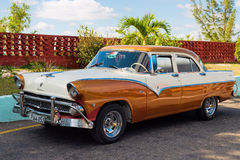 Vintage car in Cuba. Vintage american car on a parking lot beside a palm tree in Cuba Royalty Free Stock Photography