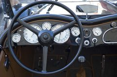 Vintage car dashboard. With white gauges and black wheel Stock Image