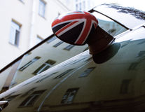Vintage car detail, concept of British Patriotism shown as flag on mirror, trees in reflection windshield Royalty Free Stock Images