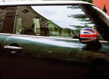 Vintage car detail, concept of British Patriotism shown as flag on mirror, trees in reflection windshield Royalty Free Stock Photo