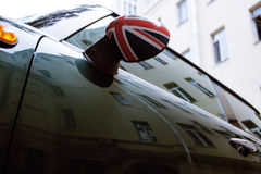Vintage car detail, concept of British Patriotism shown as flag on mirror, trees in reflection windshield, body part Stock Photos