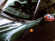 Vintage car detail, concept of British Patriotism shown as flag on mirror, trees in reflection windshield, body part. Closeup reflection stock photography
