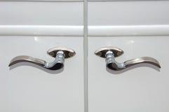 Vintage car door handles. Closeup of silver decorative vintage car door handles on a white car Stock Photo