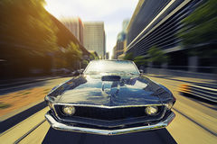 Vintage Car. Drives through a sunny cityscape setting Royalty Free Stock Images