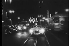 Vintage car driving on cable car tracks at night