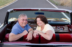 Vintage car fans. An attractive middle-aged couple smiles at the viewer over the back seat of their vintage red convertible Royalty Free Stock Photography