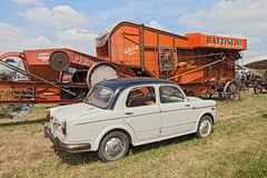 Vintage car Fiat 1100 near to an old thresher machine Stock Photography