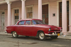 Vintage car in front of pink building in Havana, Cuba Royalty Free Stock Photos