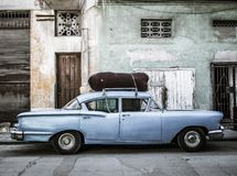 Vintage car in Havana vieja. A car parked in front of an eroding house and no-parking sign in Havana vieja Royalty Free Stock Photos