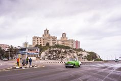 Vintage Car and Hotel Nacional de Cuba / National Hotel of Cuba. Havana, Cuba / March 21, 2016: Vintage green car on the Malecon highway in front of  historic Royalty Free Stock Photography