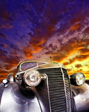 Vintage car large brightly coloured sunset. A Vintage against a car large brightly colored sunset Royalty Free Stock Photos
