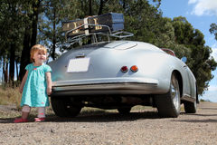 Vintage car and little girl. Vintage car. Ready for a road trip. Holiday. Blue suit-case packed for holiday. Little girl standing next to car stock images