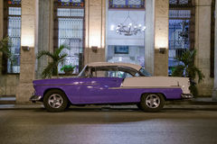 Vintage car at night In Havana, Cuba. An old american classic car parked in front of an elegant colonial building in Old Havana Stock Photos