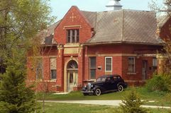 Vintage Car, Old Building. A vintage car sits quietly outside an old brick building Royalty Free Stock Image