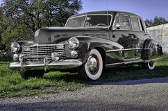 Vintage 1941 car parked on a rural Texas road. 1941 Cadillac with lots of chrome, whitewall tires and sweeping fenders parked by a shed in rural Texas Stock Images