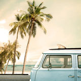 Vintage car parked on the tropical beach. Seaside with a surfboard on the roof Royalty Free Stock Photos