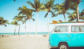 Vintage car parked on the tropical beach. Seaside with a surfboard on the roof - Leisure trip in the summer. retro color effect royalty free stock photos