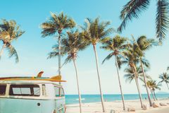 Vintage car parked on the tropical beach. Seaside with a surfboard on the roof - Leisure trip in the summer. retro color effect royalty free stock photography