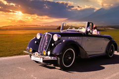 Vintage car on the road. Old veteran car on the road at sunset Royalty Free Stock Photo