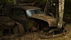 A vintage car in scrapyard in Swedish forest. royalty free stock images