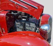Vintage car showing engine. Red vintage saloon car with hood raised ( bonnet ) showing engine details, headlight, mudguard and radiator grille Stock Images