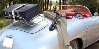 Vintage car. With suitcase on the back. Working closing hanging over the side. Ready for a road trip. Holiday stock photo