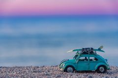 Vintage car with surf board on roof top. Nostalgic road trip concept Stock Images