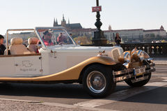 Vintage car taking tourists for a tour in the streets of Prague, with Prague Castle in the background Stock Photography