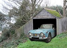 Vintage car triumph tr4 found in derelict abandoned shed garage. Photo of a pristine vintage tr4 classic car found in a derelict abandoned barn shed garage royalty free stock images