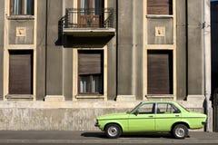 Vintage car versus facade. Green vintage car versus old building Royalty Free Stock Photography