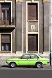 Vintage car versus facade. Green vintage car versus old building Stock Photos