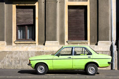 Vintage car versus facade. Green vintage car versus old building Stock Photo