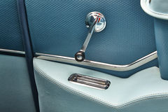Vintage car window crank and ashtray un armrest. A 1957 Chevy Belair backseat armrest in Tropical Turquoise color scheme. Window hand crank and ashtray Royalty Free Stock Photo