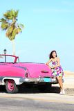Vintage car and woman happy. Vintage car and woman standing happy and smiling leaning on pink retro car on the side of the road. Beautiful young multicultural Stock Image