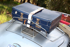 Vintage car. Working closing hanging over the side. Ready for a road trip. Holiday. Blue suit-case packed for holiday stock images
