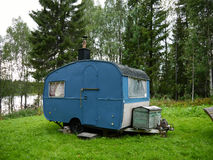 Old caravan in field. An old blue caravan in a field beside forest and river in Boden, Sweden Royalty Free Stock Photo