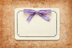 Vintage card with lilac bow. On old grunge paper background Royalty Free Stock Photo