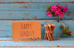 Vintage card with phrase: happy sunday and stack of wooden colorful pencils on wooden texture table Royalty Free Stock Images