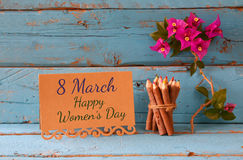Vintage card with phrase: 8 march happy womens day on wooden texture table next to purple bougainvillea flower. Royalty Free Stock Image