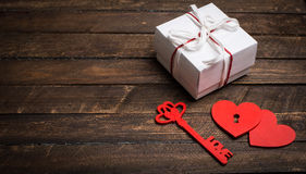 Vintage card with red hearts, key and gift box on old wood. Vale Royalty Free Stock Photography
