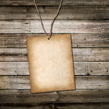 Vintage cardboard card on a rope. Wooden background Royalty Free Stock Photography