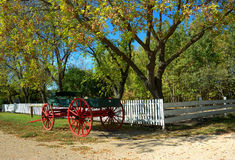 Vintage Carriage. A vintate horse drawn carriage rests by white picket fence Royalty Free Stock Image