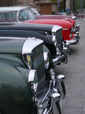 Vintage cars bonnets line. 4 old cars parked on street Royalty Free Stock Photography