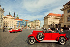 Vintage cars drive around royal palaces of 9th century Prague castle. UNESCO World Heritage Register Royalty Free Stock Image