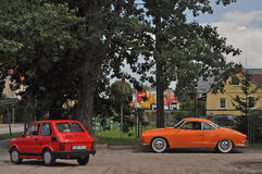 Vintage cars Fiat 126 and Volkswagen parked. Old Polski Fiat 126p and Volkswagen karmann Ghia automobiles from parked during old cars race in Northern Poland Stock Image